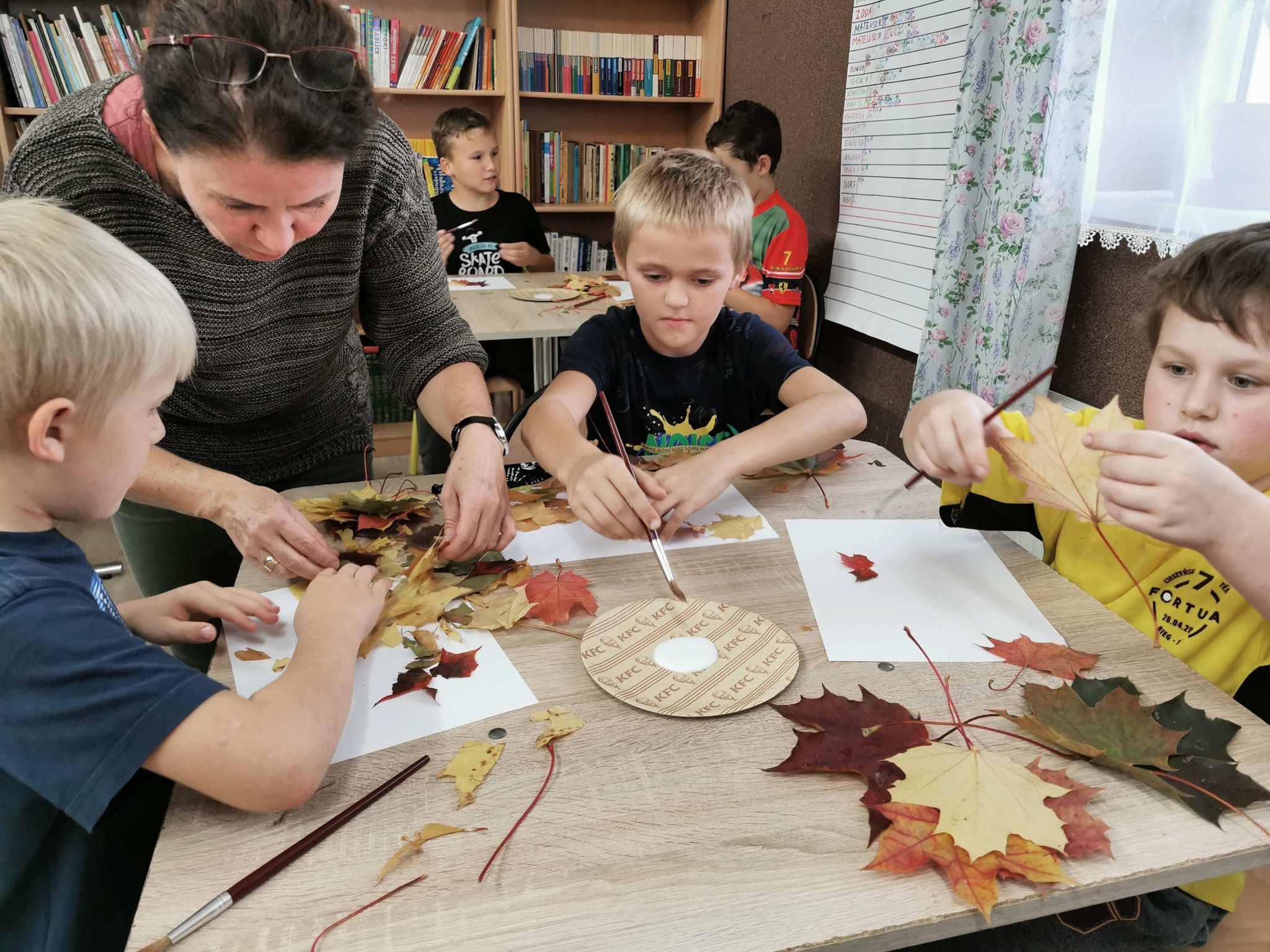 Dzieci wykonujące prace plastyczne z liści